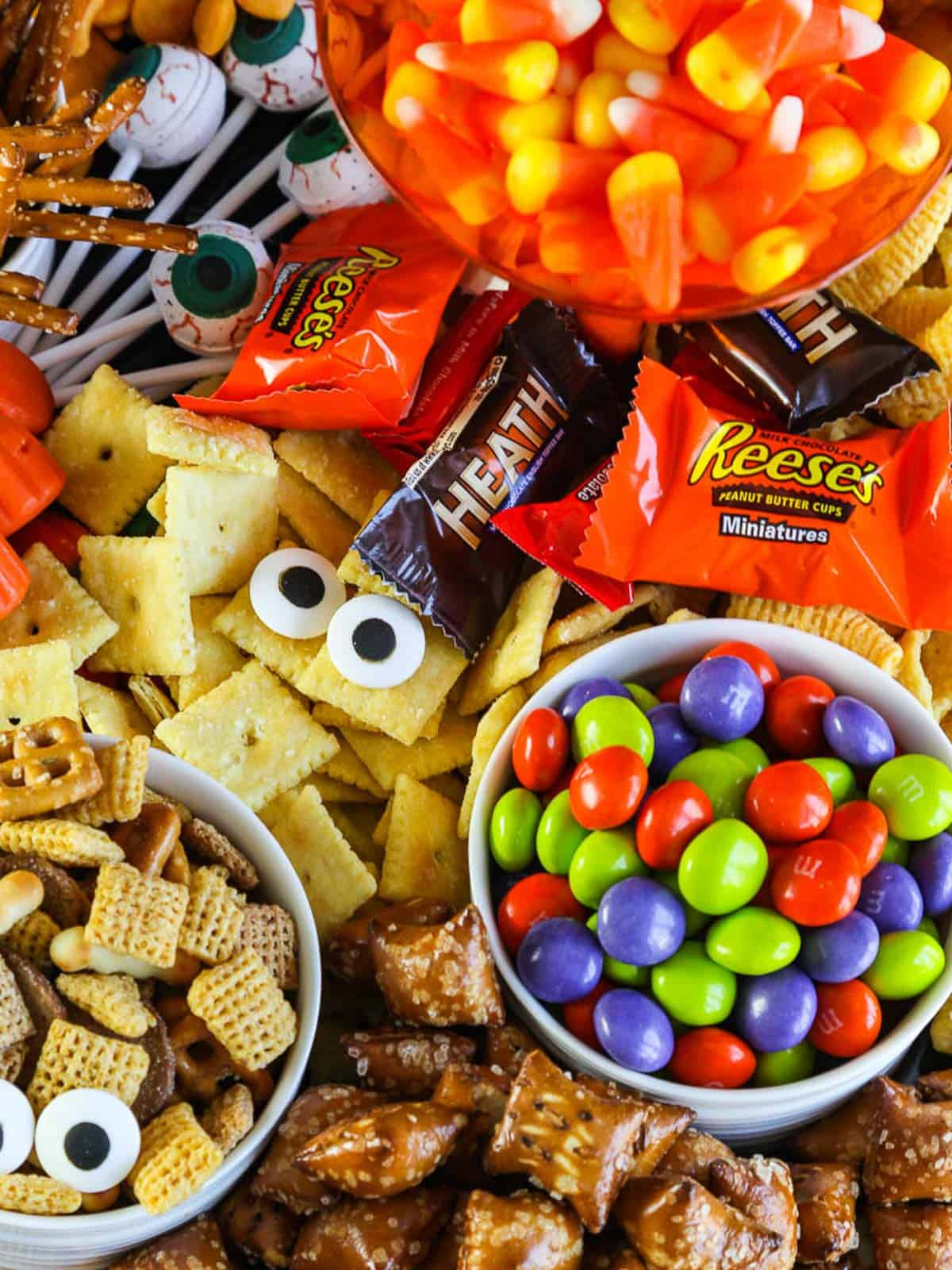 A variety of sweet and salty Halloween Snacks with candy eyeballs.