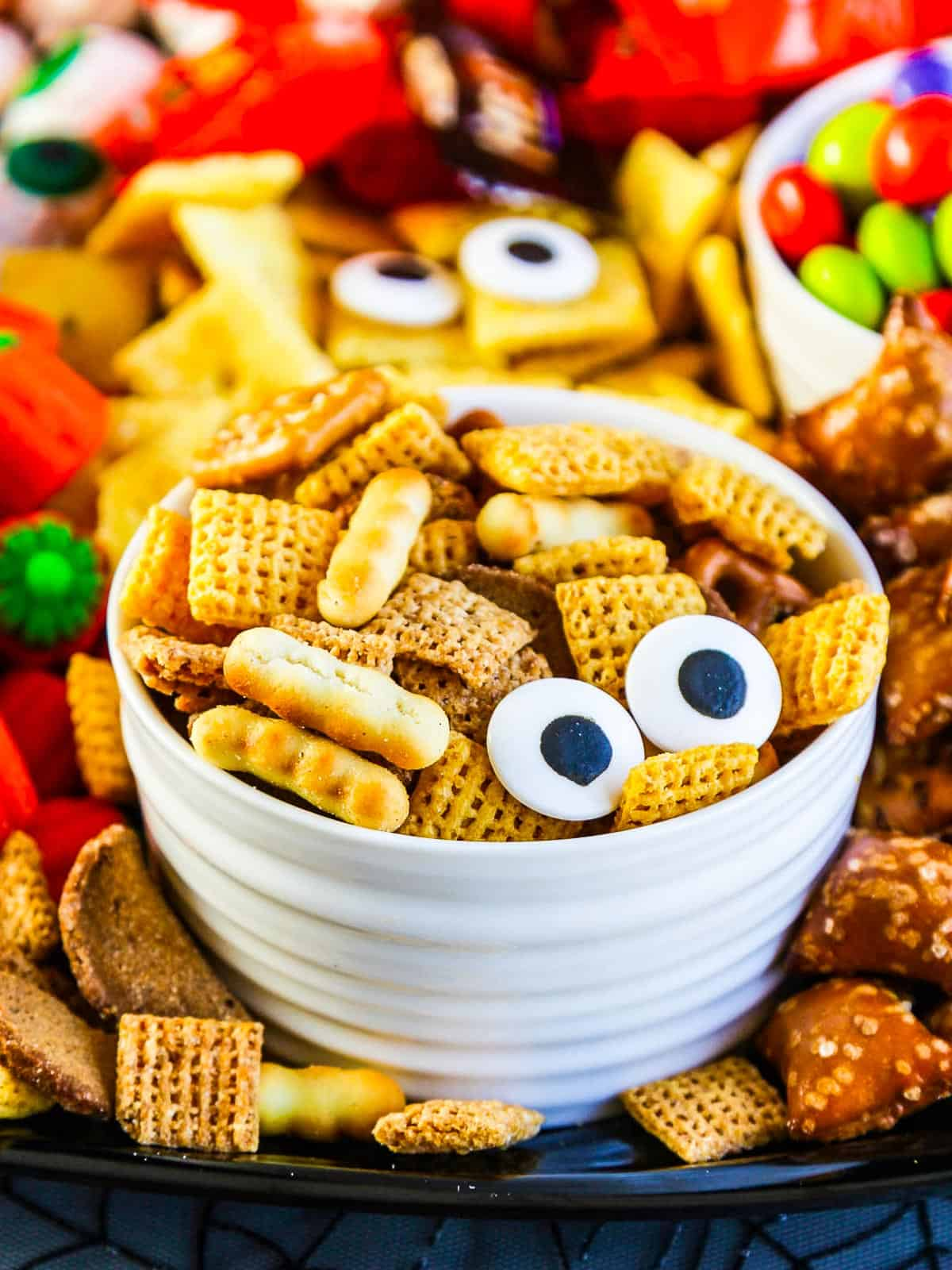 A small white bowl with chex mix and two candy eyeballs for a Halloween Snack.