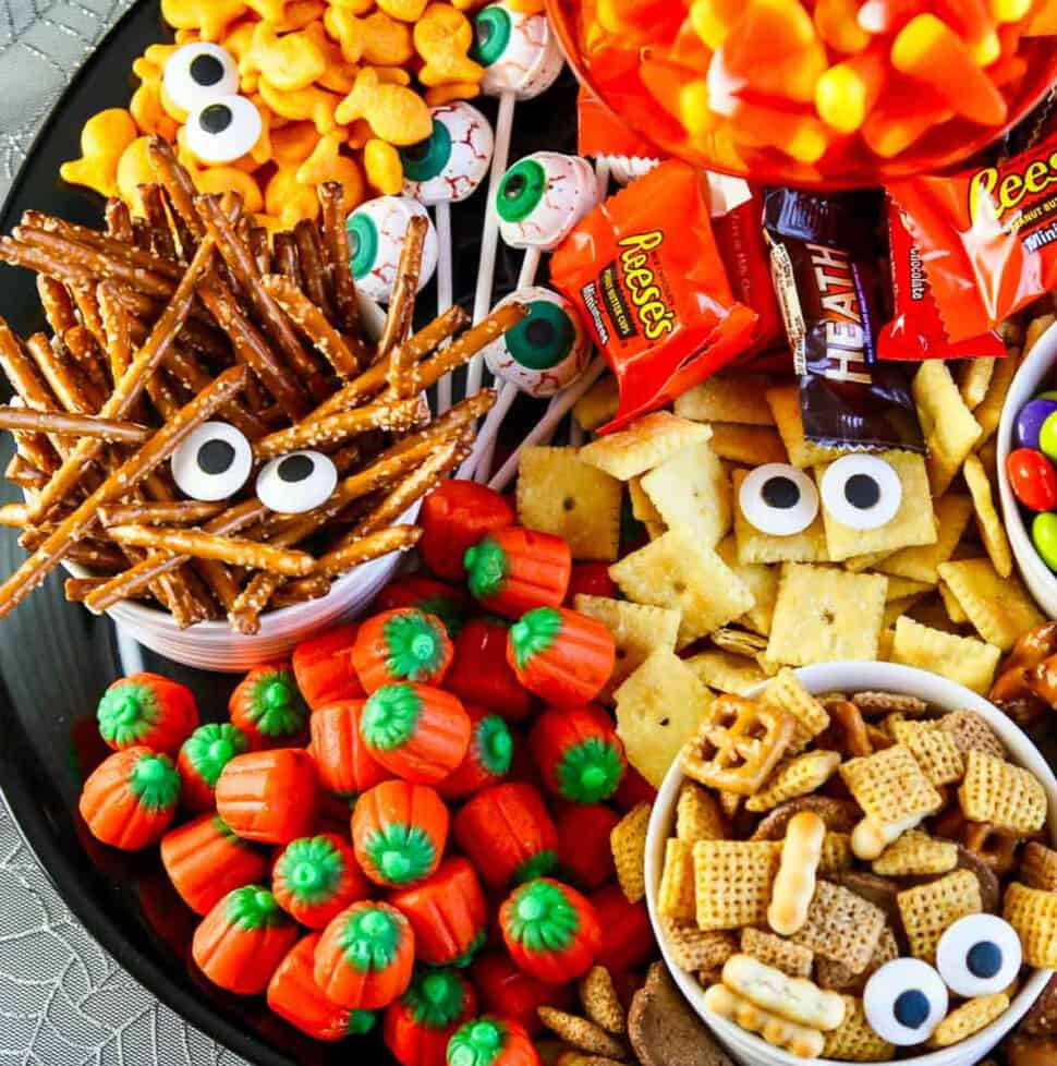 A full platter of Halloween salty snacks and candy decorated with candy eyeballs for an easy last minute Halloween Party Idea.