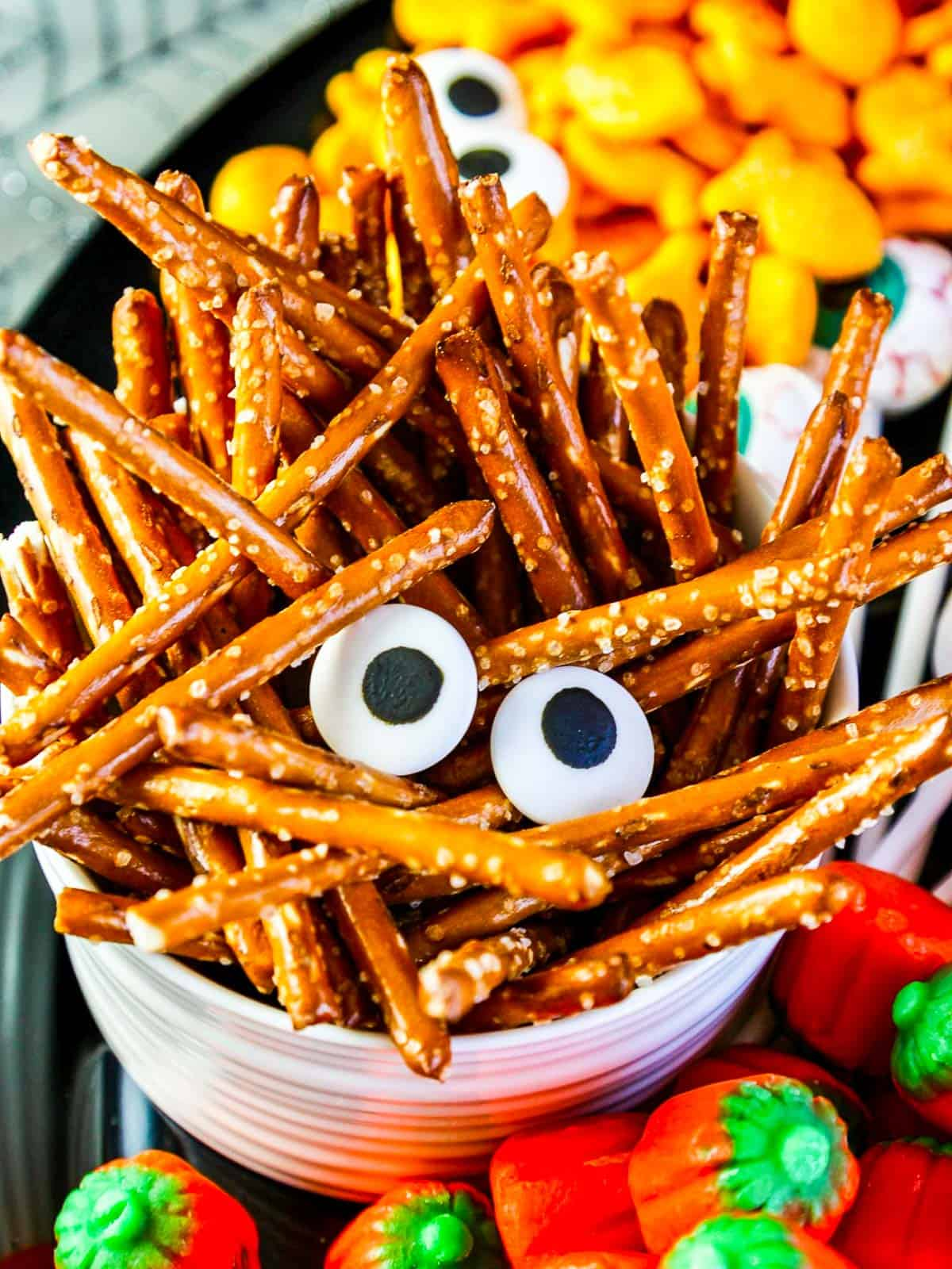Pretzel sticks piled into a small white bowl with candy eyes for a Halloween Snack.