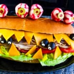 A giant sub sandwich that looks like a Monster with giant edible radish eyes and small black olive eyes.