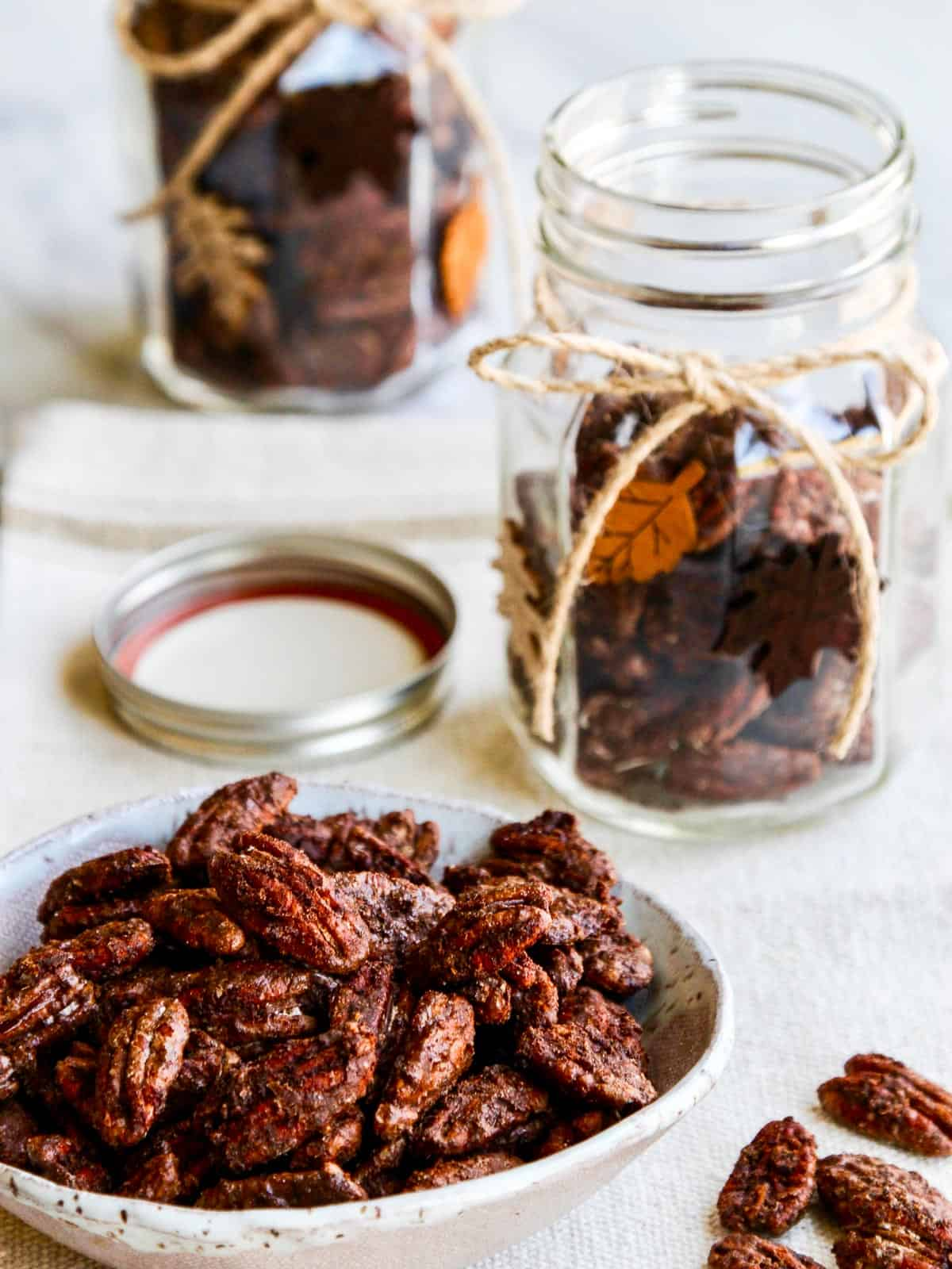 A white bowl of spicy candied pecans with two decorated gift jar nearby being filled.
