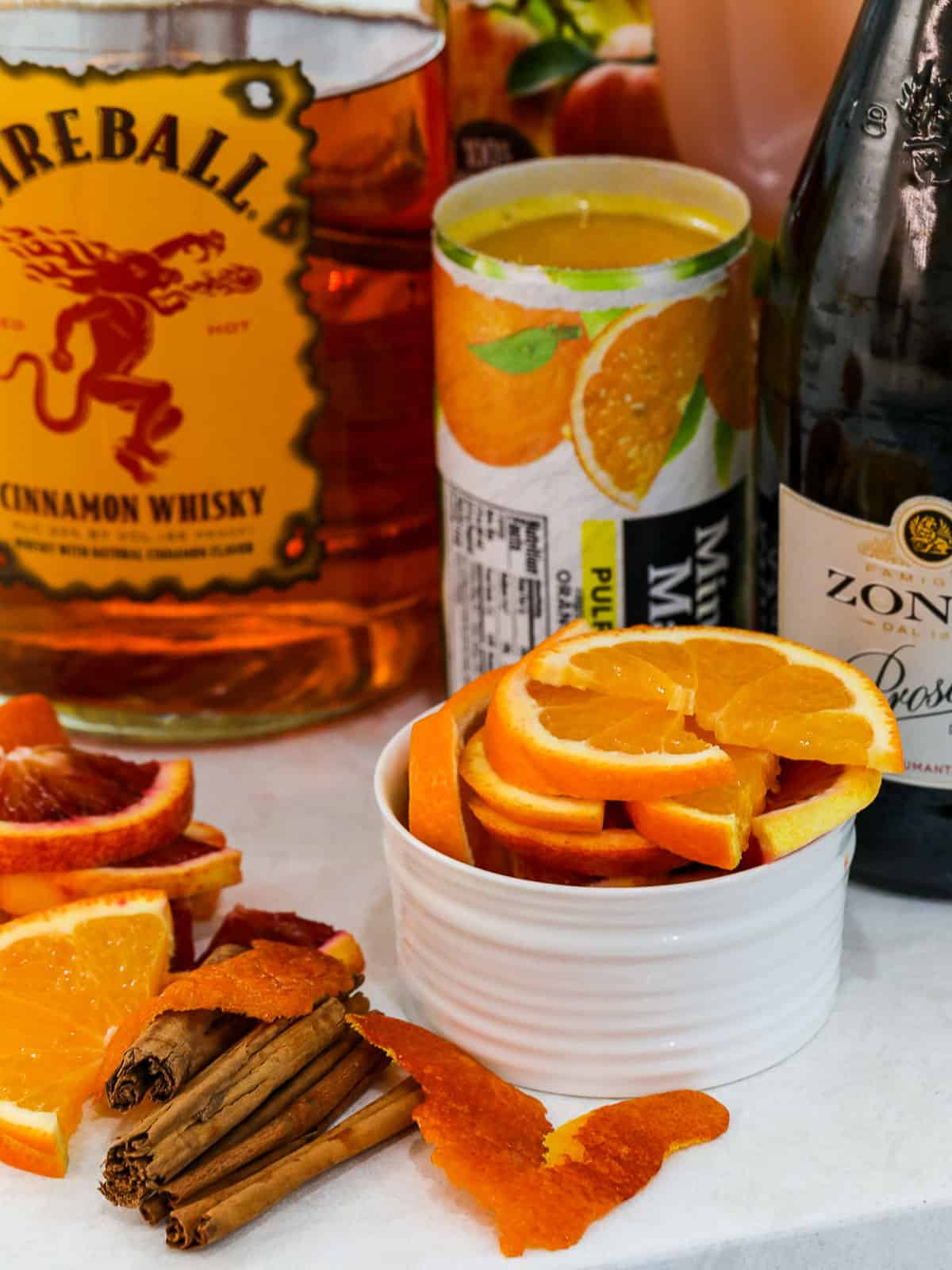 Ingredients to make Fireball punch; orange juice concentrate, Prosecco, Fireball Whisky, and apple cider.
