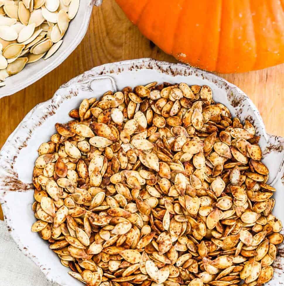 A ceramic dish full of golden brown roast pumpkin seeds.