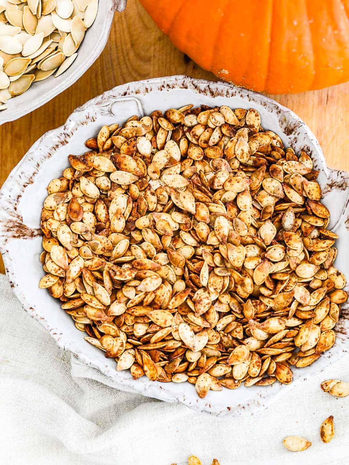 A ceramic bowl filled with seasoned roast pumpkin seeds.
