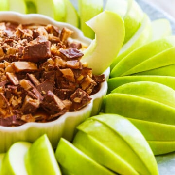 Slices of green Granny Smith apples around a white dish with a sweet dessert dip inside a low small white dish with a ruffled edge, and a piece of apple sticking into the dip.