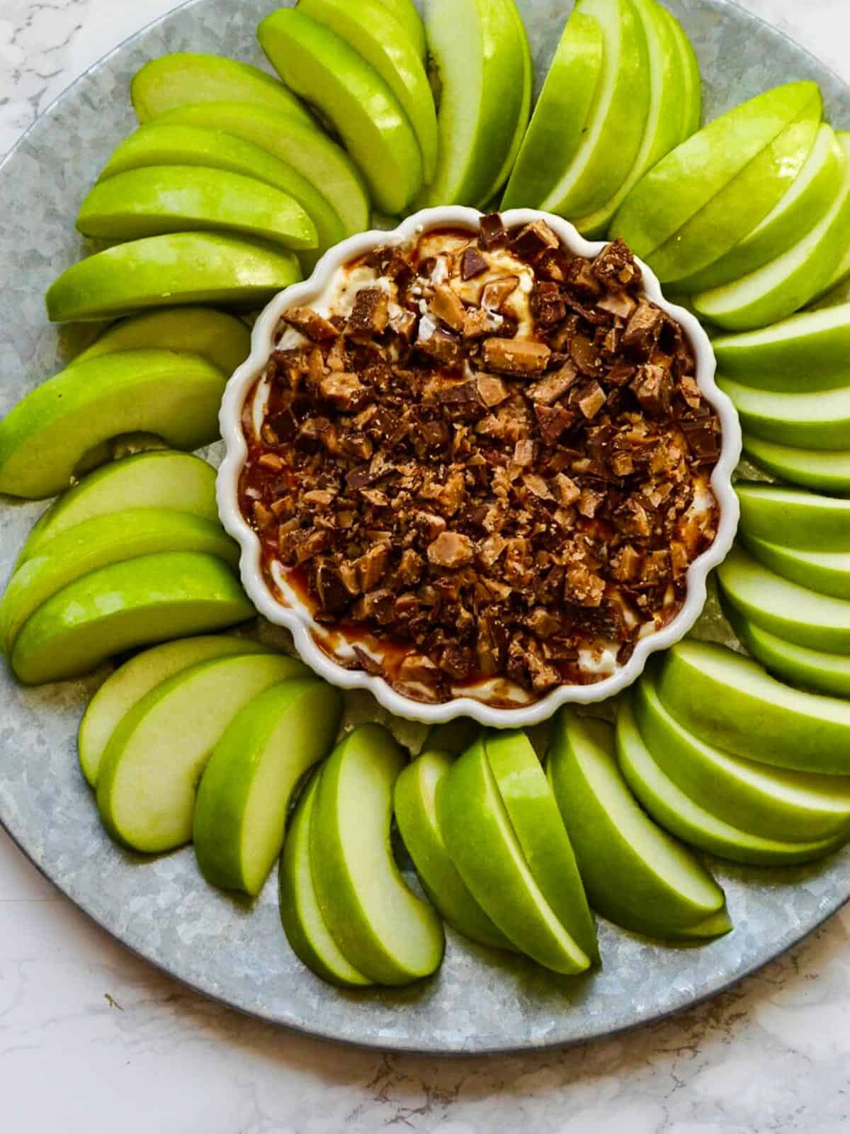 A large silver platter with green apple slices layed into a circular pattern around a white dish holding a sweet caramel apple dip for dessert topped with crushed Heath candy bars.