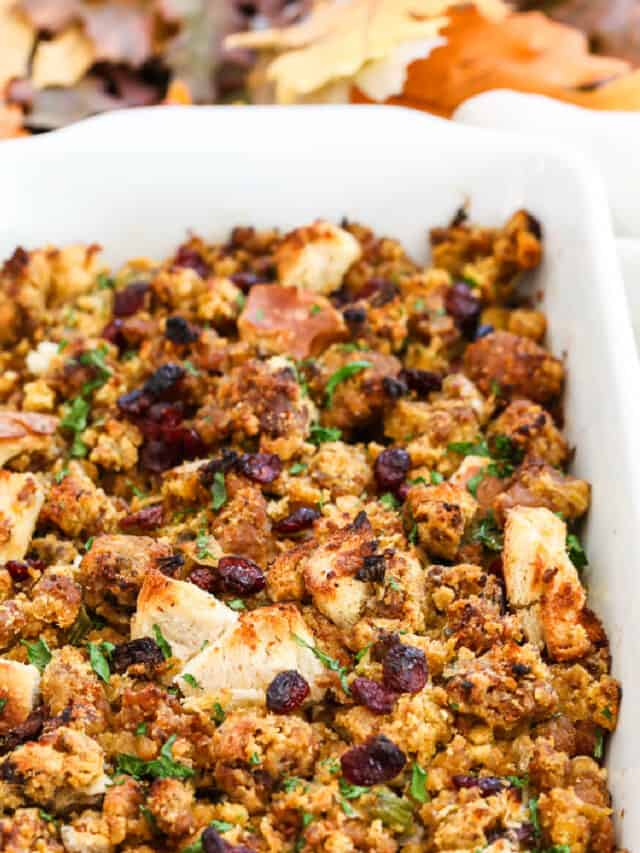 A white casserole dish filled with Sausage Stuffing baked to a golden brown.