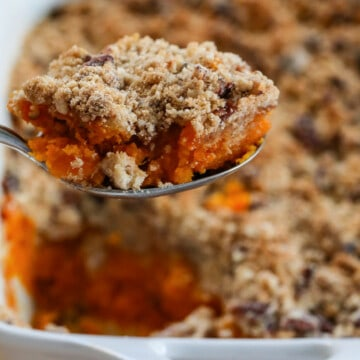 Lifting a scoop of sweet potato casserole out of a white casserole dish with large serving spoon.