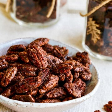A white bowl with candied pecans and a few on the table with jars filled with them nearby.