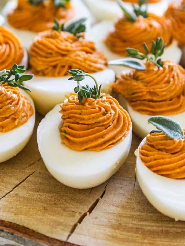 A slice of rustic tree wood with Thanksgiving deviled eggs garnished with fresh herbs.