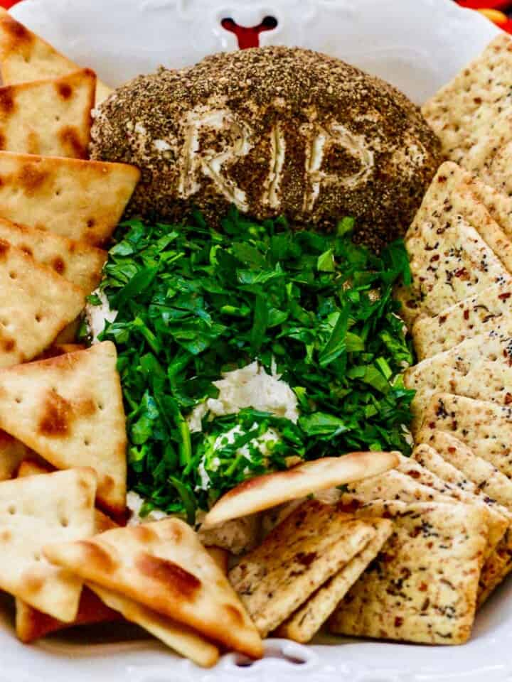 A cracker scooping out some Halloween dip shaped like a tombstone in a white dish.