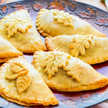 Golden brown baked empanadas decorated with pie crust leaves on a Fall tray.