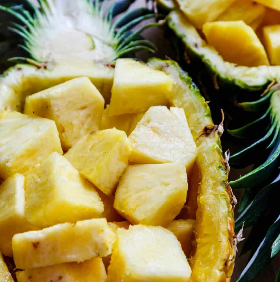 A pineapple bowl filled with fresh cut chunks of pineapple ready to eat.