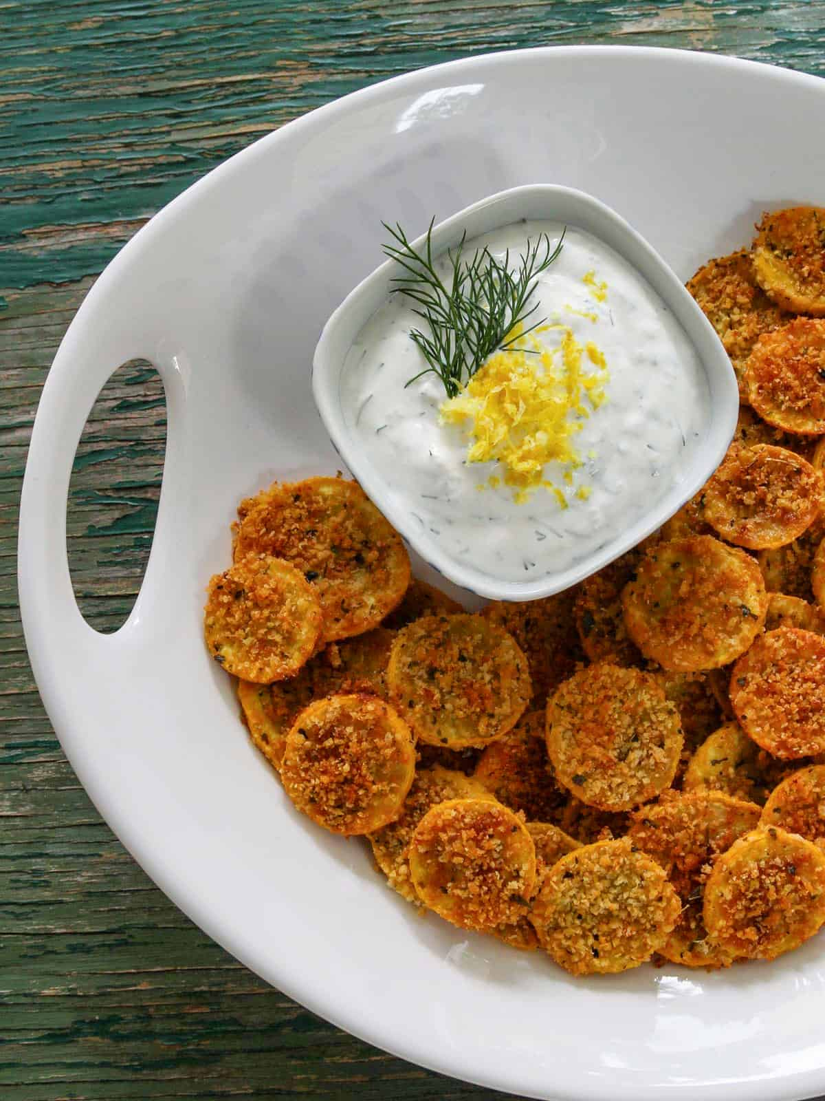 A large white platter with zucchini chips on it and a small bowl of yogurt dip garnished with lemon and dill.