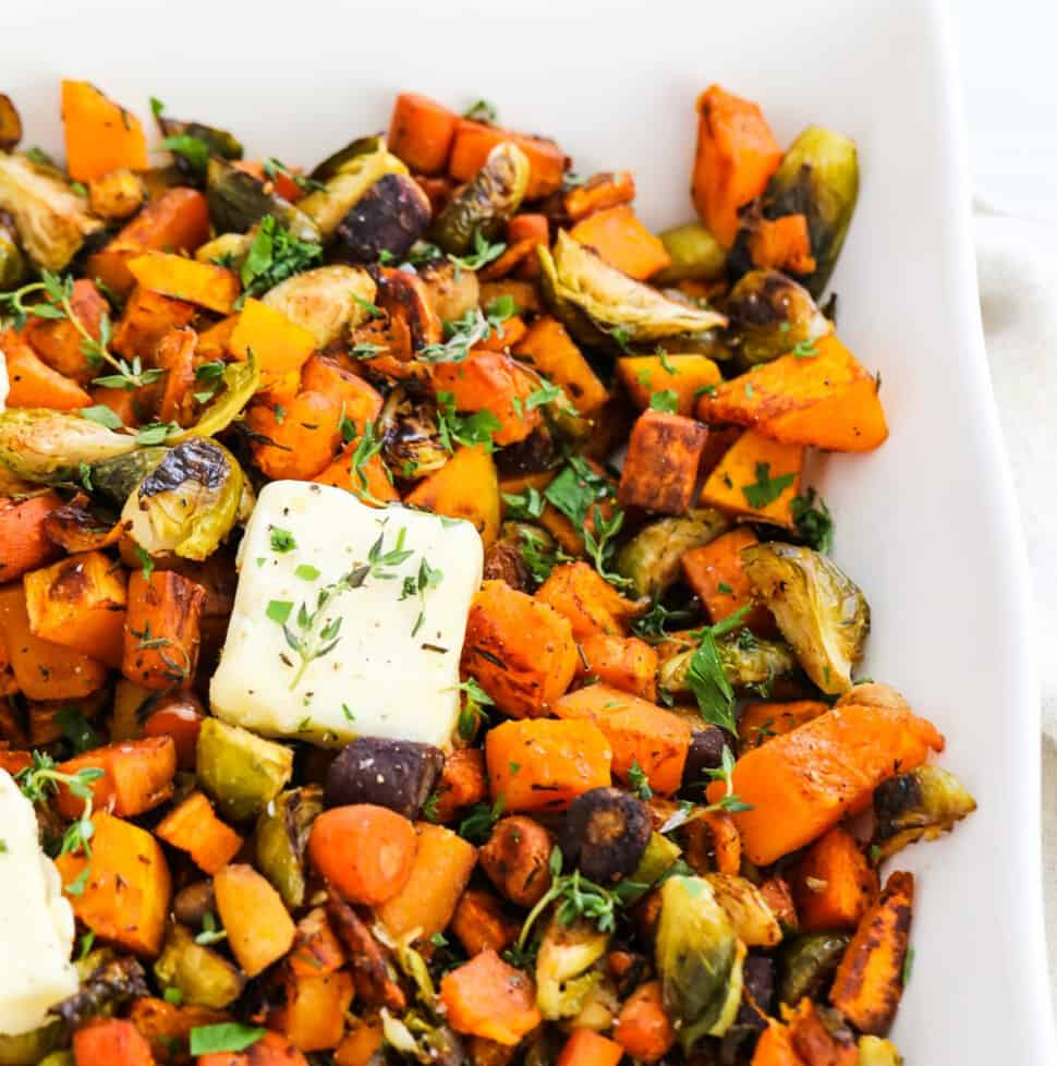 A square white dish filled with colorful roasted vegetables and topped with squares of butter garnished with herbs.