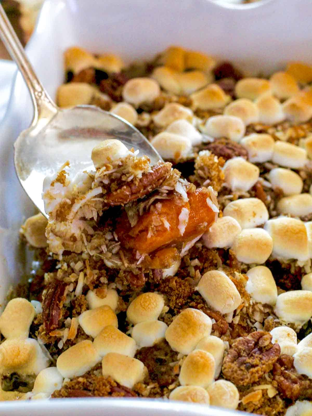 A silver server scooping up sweet potato casserole with golden toasted marshmallows on top out of a white casserole dish.
