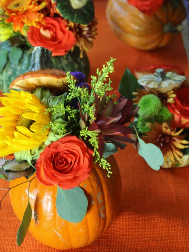 An orange table runner with handmade orange pumpkins filled with fresh Fall flowers and greenery for Thanksgiving centerpieces.