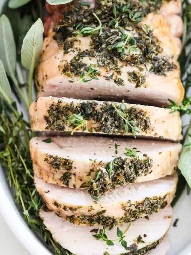Top down view of a roasted turkey breast sliced thick and garnished with fresh herbs.