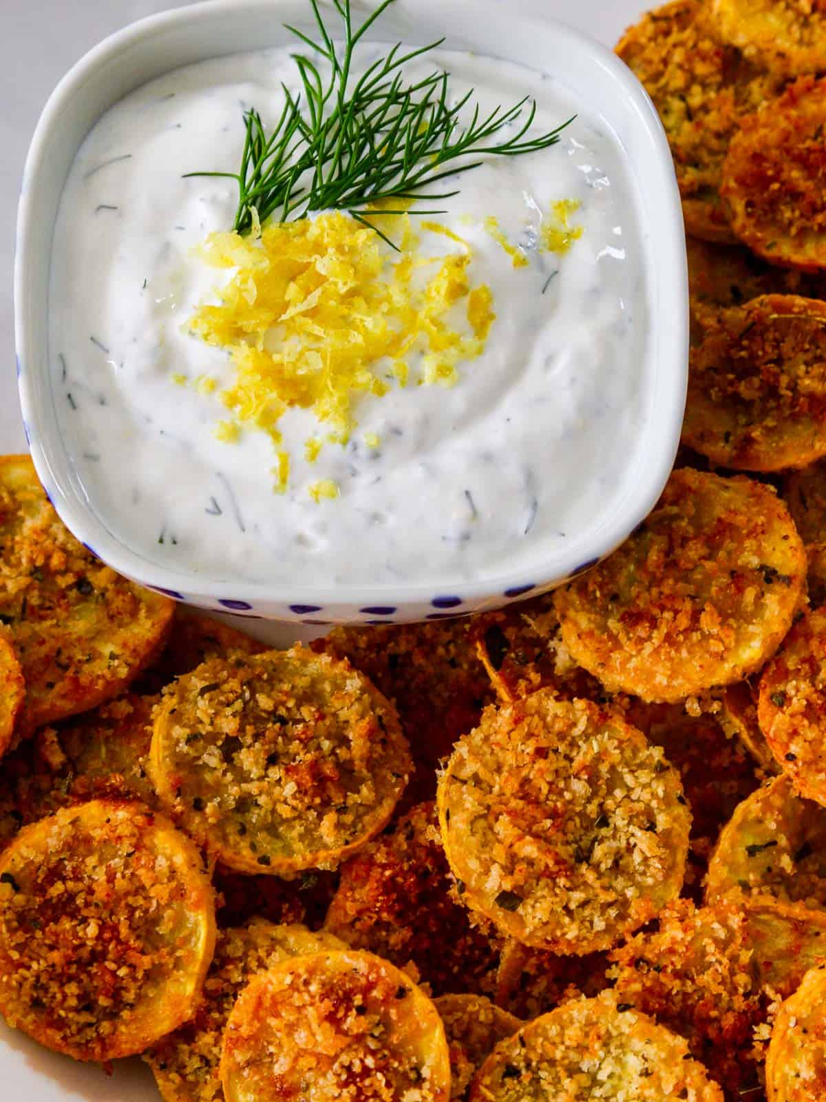 Looking down on a plate of zucchini chips with a yogurt dip garnished with fresh dill and lemon zest.