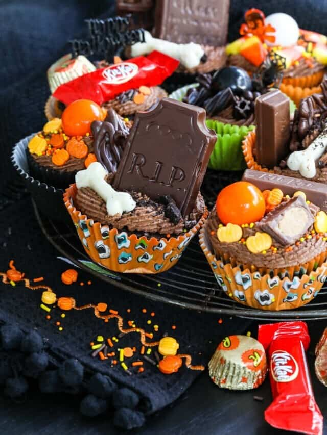 Halloween cupcakes on a wire rack decorated with candy, gumballs, Halloween toys and chocolate tombstones.